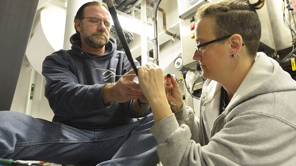 Chris Griner and Amy Simoneau test one of the three optical fibers at the center of the .681 cable.
